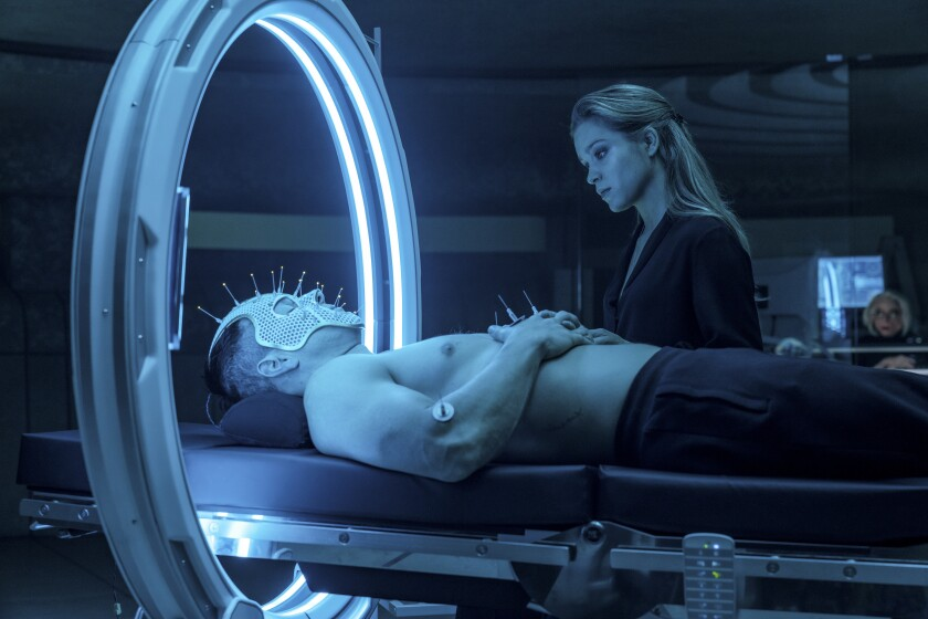 """Mark Wahlberg tests out some high-tech acupuncture while Sophie Cookson looks on in the movie """"Infinite."""""""