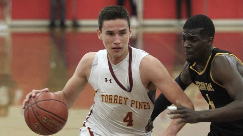 Torrey Pines' Bryce Pope drives against Mission Bay's Jay Norton Wednesday during the San Diego Sect