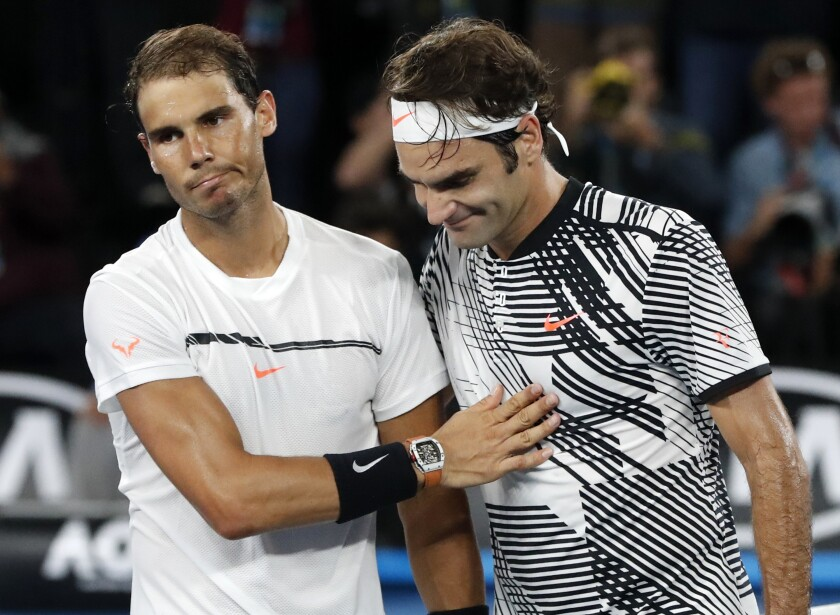 Switzerland's Roger Federer, right, and Spain's Rafael Nadal share a moment on the pitch.