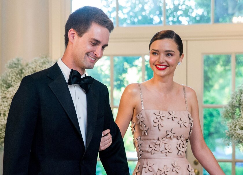 FILE - In this May 13, 2016 file photo, model Miranda Kerr, right, and her boyfriend, Snapchat CEO Evan Spiegel, arrive for a state dinner for Nordic leaders at the White House in Washington. Kerr announced on her Instagram account, Wednesday, July 20, that the couple are engaged. This will be the