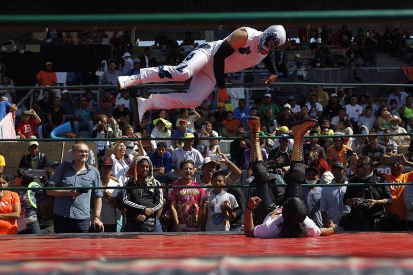 Miembros de la caravana migrante observan un espectáculo de lucha libre hoy, viernes 9 de noviembre de 2018, en Ciudad de México (México). EFE