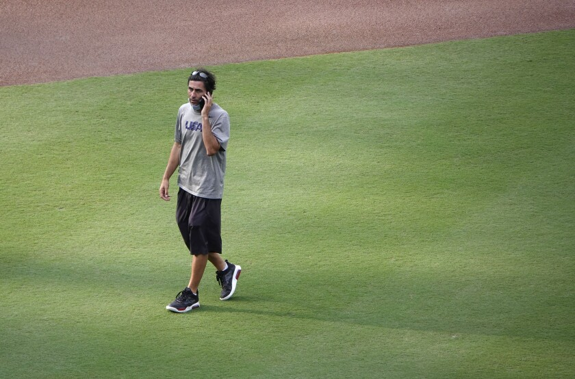 Padres General Manager A.J. Preller talks on the phone as he crosses the Petco Park infield.