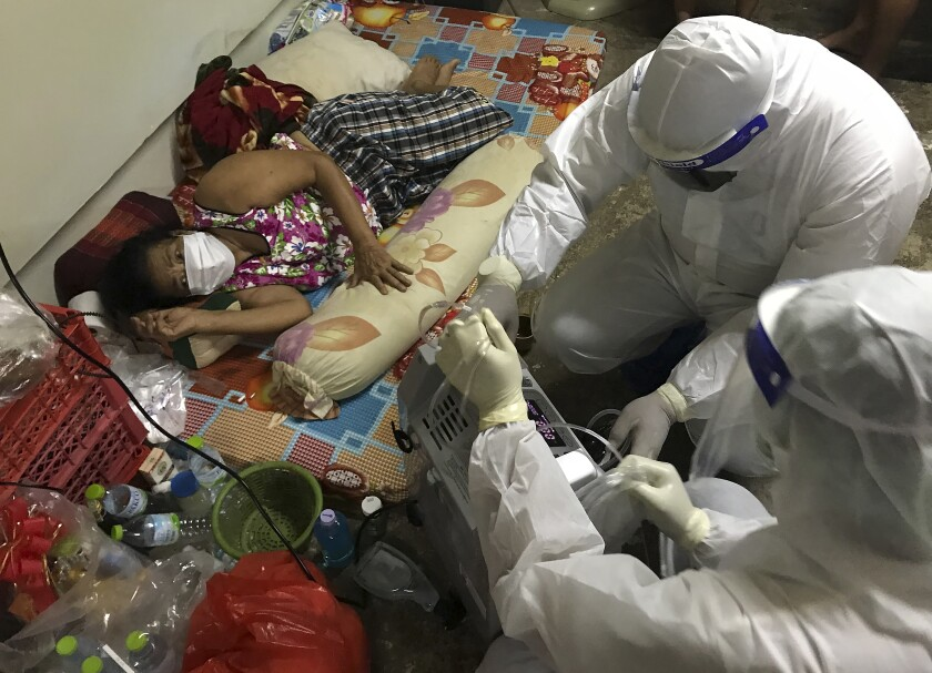 """Volunteers from the """"Saimai Will Survive"""" group in protective gear prepare oxygen for a struggling woman infected with COVID-19 on July 23, 2021, in Bangkok, Thailand. As Thailand's medical system struggles beneath a surge of coronavirus cases, ordinary people are helping to plug the gaps, risking their own health to bring care and supplies to often terrified, exhausted patients who've fallen through the cracks. (AP Photo/Tassanee Vejpongsa)"""