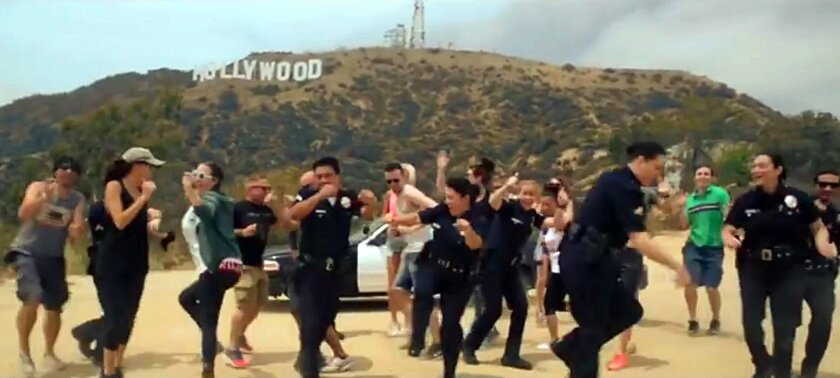 In this undated frame from video provided by the Los Angeles Police Department, LAPD officers and others dance beneath the iconic Hollywood Sign in Los Angeles. In a now-viral sensation, police officers across the U.S. are dancing an updated version of the running man to a catchy 1990s hip hop song
