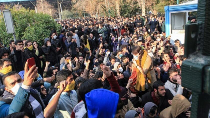 Protesters at Tehran University confront anti-riot police in Tehran on Dec. 30, 2017.