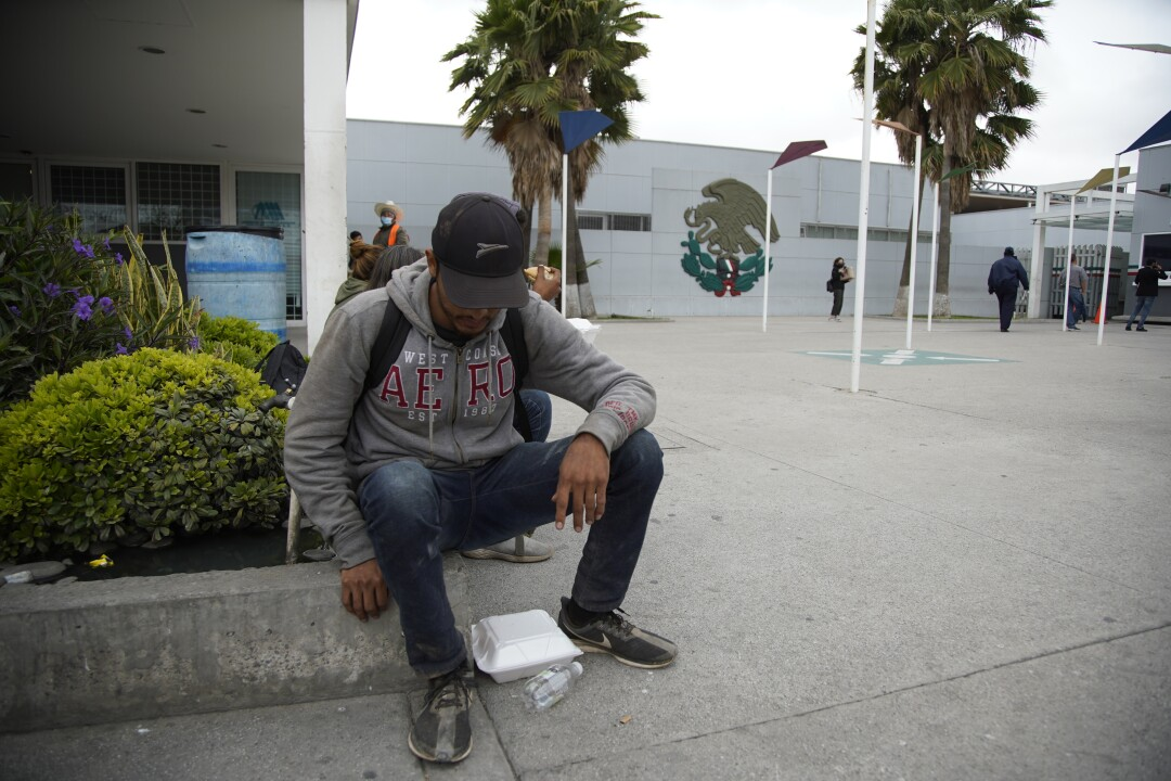 Francisco, recently expelled, sits near the pedestrian crossing to eat lunch from a Styrofoam container