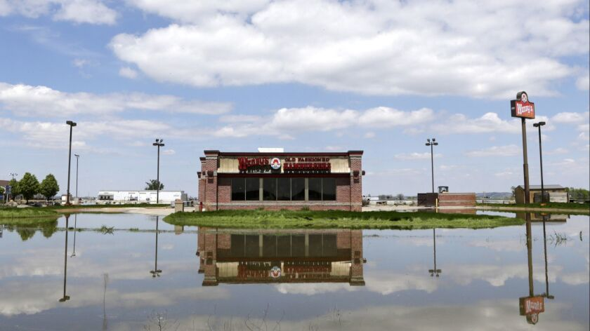 A Wendy's store in Percival, Iowa, is reflected in floodwaters from the Missouri River, Friday, May