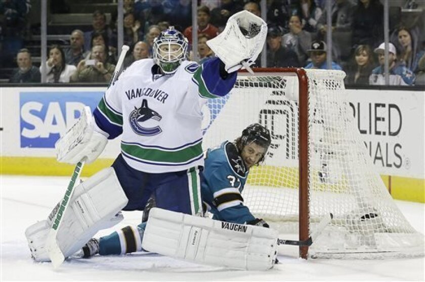 Vancouver Canucks goalie Cory Schneider (35) catches the puck in front of San Jose Sharks right wing Adam Burish (37) during the first period of an NHL hockey game in San Jose, Calif., Monday, April 1, 2013. (AP Photo/Jeff Chiu)