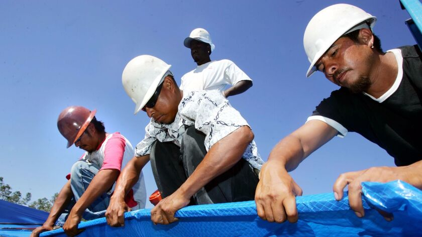 Immigrant workers install a plastic tarp as temporary protection for a home damaged by Hurricane Katrina in Gulfport, Miss. on Oct. 23, 2005.