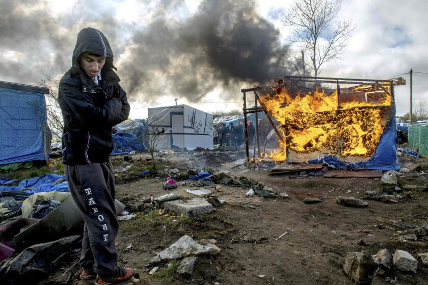 A man stands by as a makeshift shelter burns in the so-called Jungle migrant camp in the French port city of Calais on Thursday.