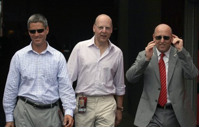 FILE - This Sept. 13, 2009, file photo shows Tampa Bay Buccaneers general manager Mark Dominik, left, co-chairmen Edward Glazer, center, and Bryan Glazer entering the field before an NFL football game against the Dallas Cowboys, in Tampa, Fla. On Friday, March 5, 2010, pro football's salary cap dies. Free agency begins under a whole new set of rules, and no one is sure where it will lead _ perhaps even to a work stoppage in 2011. (AP Photo/Reinhold Matay, File)