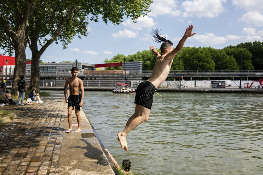 Youths dive in the Canal de l'Ourcq Wednesday, June 16, 2021 in Paris. Temperatures rose up to 33 degrees Celsius (91 degrees Fahrenheit) in the French capital. (AP Photo/Benjamin Girette)