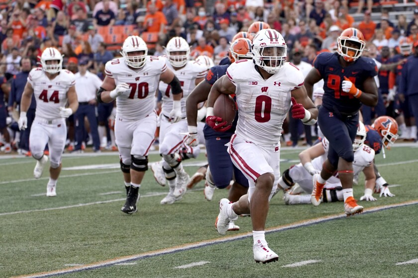 Wisconsin running back Braelon Allen heads for the end zone for a touchdown during the second half of an NCAA college football game against Illinois on Saturday, Oct. 9, 2021, in Champaign, Ill. Braelon Allen is only 17 years old, but the 6-foot-2, 238-pound freshman running back already is earning a reputation for his bruising approach each time he carries the ball. (AP Photo/Charles Rex Arbogast)