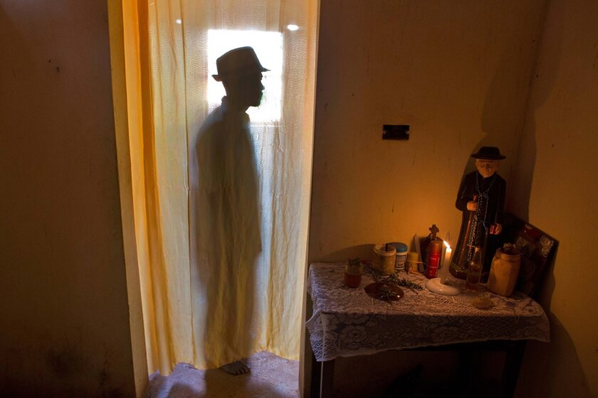 """In this Feb. 2, 2016 photo, Jose Esteves, 63, stands next to his statue of """"Padre Cicero"""" as he prepares spiritually for Carnival celebrations inside his home in Nazare da Mata, Brazil. Padre Cicero is venerated here as a saint but not recognized as one by the Roman Catholic Church. (AP Photo/Erald"""