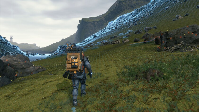 "A character walks on a grassy mountainside in ""Death Stranding."""