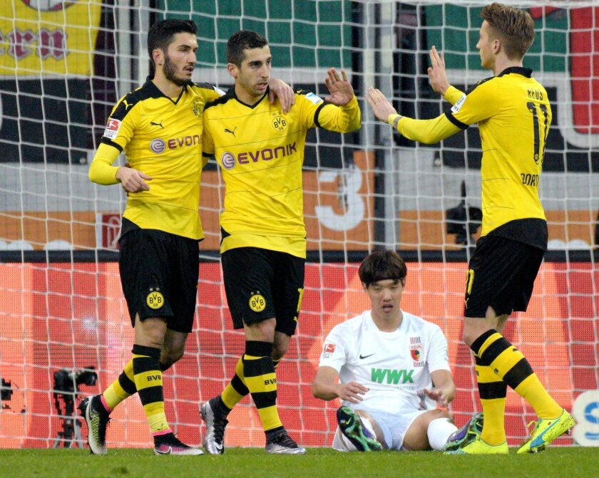 Dortmund's scorer Henrikh Mkhitaryan, 2nd left, and his teammates Nuri Sahin, left, and Marco Reus, right, celebrate their side's first goal during the German Bundesliga soccer match between FC Augsburg and Borussia Dortmund in Augsburg, Germany, Sunday, March 20, 2016. (Stefan Puchner/dpa via AP)