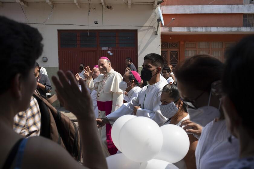 Monsignor Franco Coppola greets people as he arrives to meet families and celebrate Mass in Aguililla, Mexico.