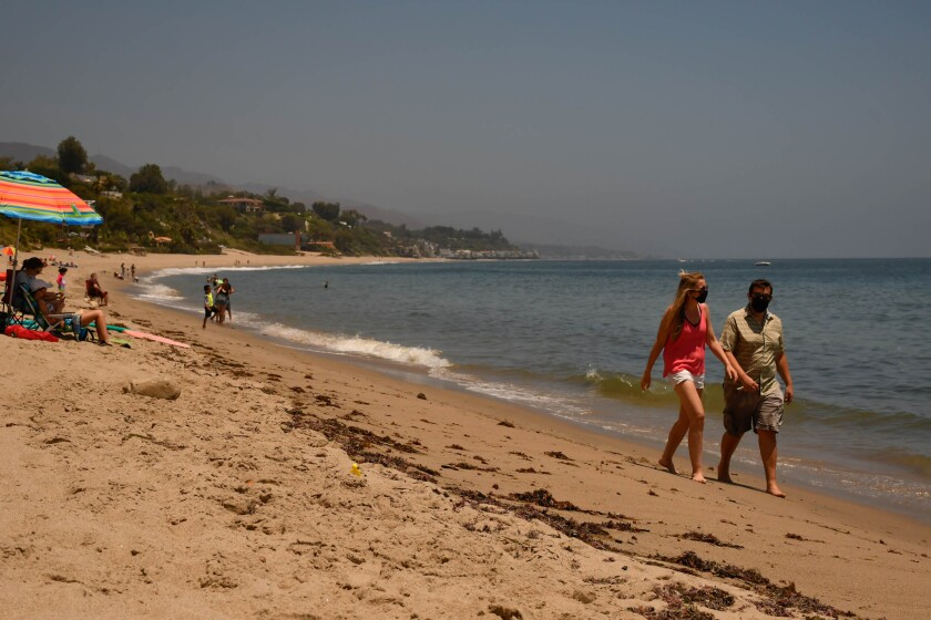 Beachgoers wear masks at Paradise Cove, Malibu.