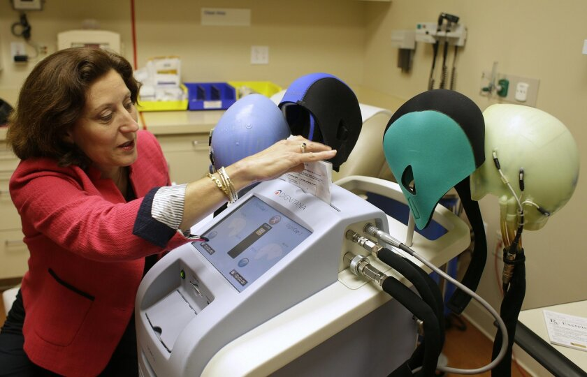 In this July 10, 2013 file photo, Dr. Hope Rugo, an oncologist and breast cancer specialist, demonstrates the use of a Dignitana DigniCap system at the University of California San Francisco Mount Zion Hospital cancer center in San Francisco. Hair loss is one of the most despised side effects of chemotherapy, and now breast cancer patients are getting a new way to save their locks. The Food and Drug Administration said Dec. 8, 2015, it would allow marketing of the DigniCap to chill patients' scalps — using a cap connected to a cooling machine — as they receive chemo. A study found it significantly reduced hair loss.(AP Photo/Eric Risberg, File)