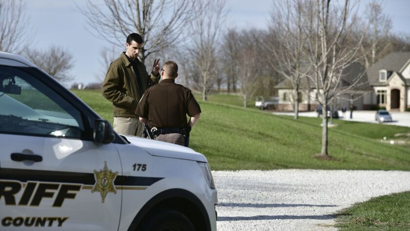 A Tazewell County sheriff's deputy talks with an unidentified man at the driveway of a home in Morton, Ill., that belongs to the extended family of Waffle House shooting suspect Travis Reinking.