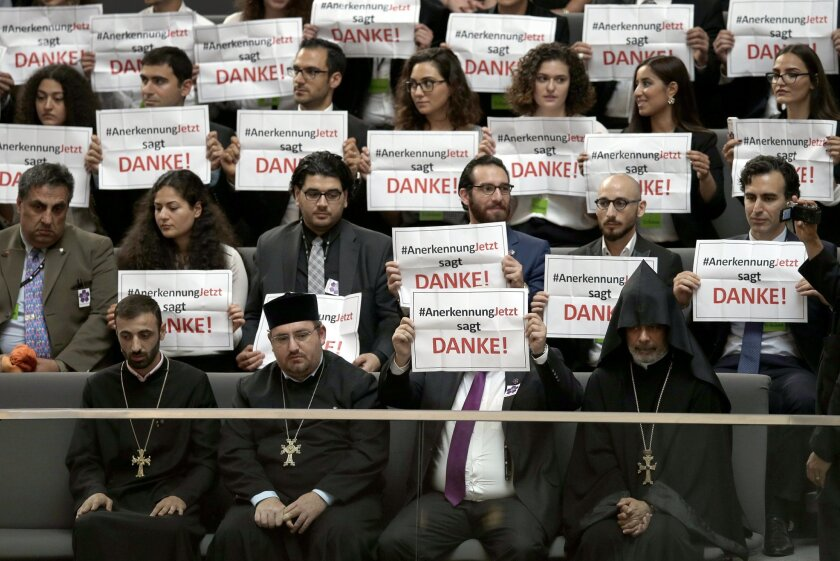 "Guests hold posters of the 'recognition now' organization reading ""RecognitionNow says Thank you"" during a meeting of the German Federal Parliament, Bundestag,  in Berlin, Germany, Thursday, June 2, 2016. The German Parliament is to vote Thursday on whether to label the killings of Armenians by Ott"