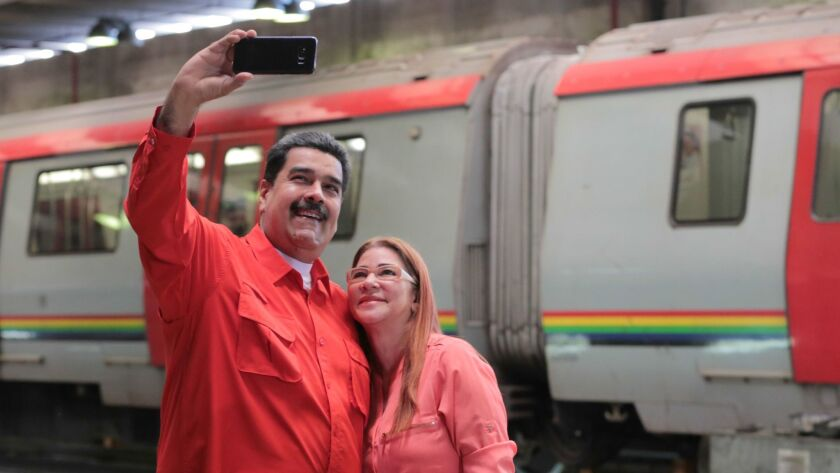 Venezuelan President Nicolas Maduro takes a selfie with his wife Cilia Flores at an event in Caracas on Jan. 24. Maduro confirmed he will seek a second term as president.