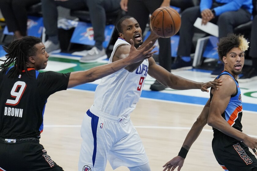 Clippers center Serge Ibaka reaches for a rebound between Thunder center Moses Brown and forward Charlie Brown Jr.