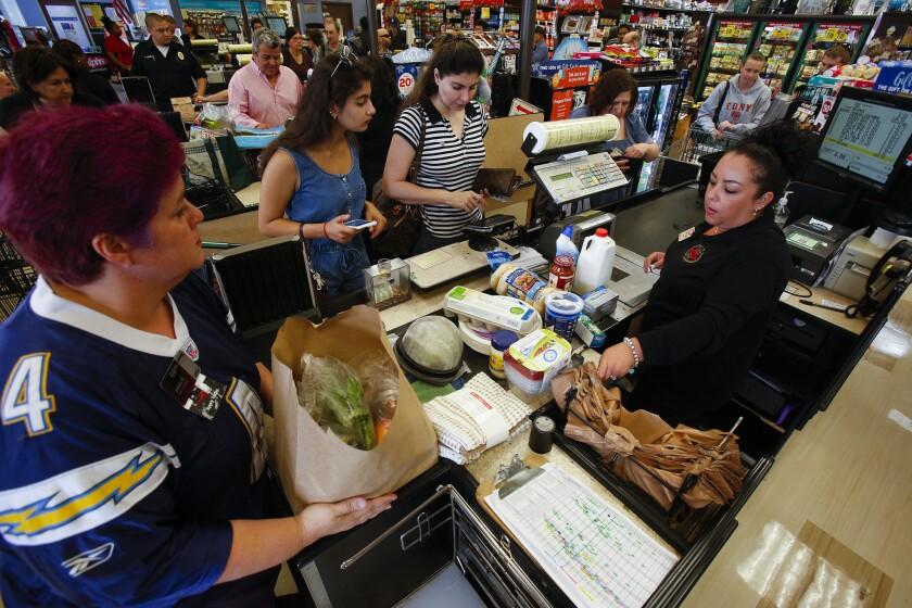 Unos clientes en un supermecado Ralphs del centro de la ciudad hacen su compra.