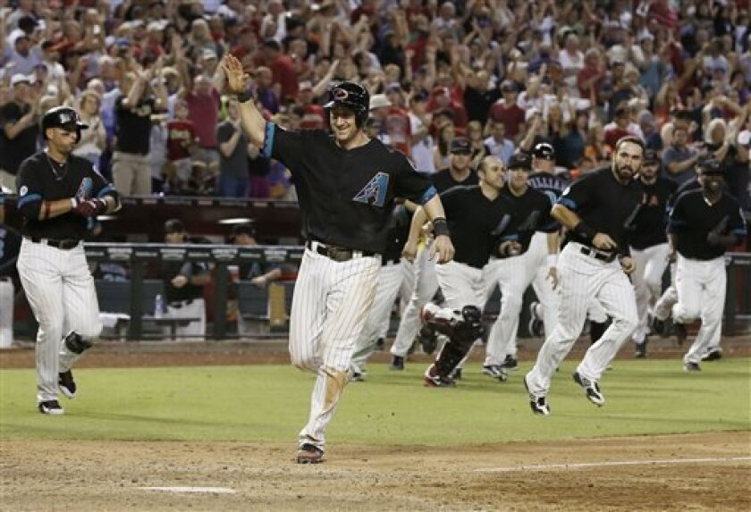 Arizona Diamondbacks' Willie Bloomquist raises his arm as he comes in to score the winning run against the San Francisco Giants in the ninth inning of a baseball game on Saturday, Aug. 31, 2013, in Phoenix.  The Diamondbacks defeated the Giants 4-3. (AP Photo/Ross D. Franklin)