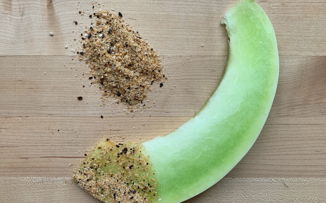 A slice of  honeydew melon dipped in a spice mix.