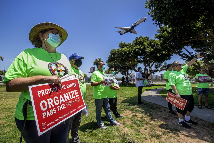 Nicole Moore, left, a driver for Lyft, joins other rideshare drivers during a rally at LAX.