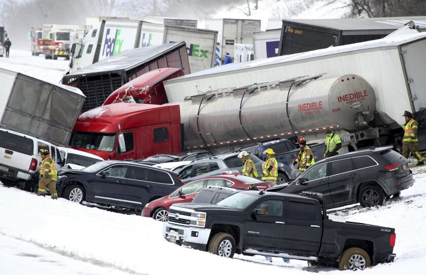Emergency personnel work at the scene of a fatal crash near Fredericksburg, Pa., Saturday, Feb. 13, 2016. The pileup left tractor-trailers, box trucks and cars tangled together across several lanes of traffic and into the snow-covered median. (Daniel Zampogna/PennLive.com via AP) MANDATORY CREDIT;