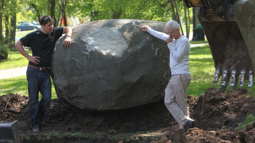 British artist Andy Goldsworthy, right, looks on as the hole for his art installation is dug deeper