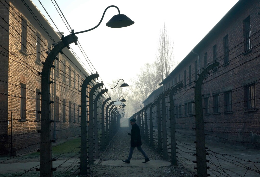 A man walks by the barbed-wire fence of Auschwitz in December.