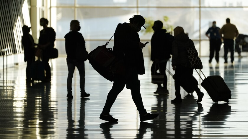 FILE - In this Oct. 27, 2020, file photo, passengers walk through Salt Lake City International Airport, in Salt Lake City. Business travel might never look the same in the wake of the coronavirus. Consulting firm McKinsey and Co. says it took international business travel five years to recover after the 2008 recession. But this time, the ease of videoconferencing could put a permanent dent in corporate trips. (AP Photo/Rick Bowmer, File)