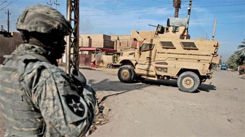 MIXED BLESSING: A U.S. Army infantryman heads back to an MRAP vehicle while on patrol. The vehicles improve safety, but they're cumbersome and are said to hamper mingling with Iraqi citizens.