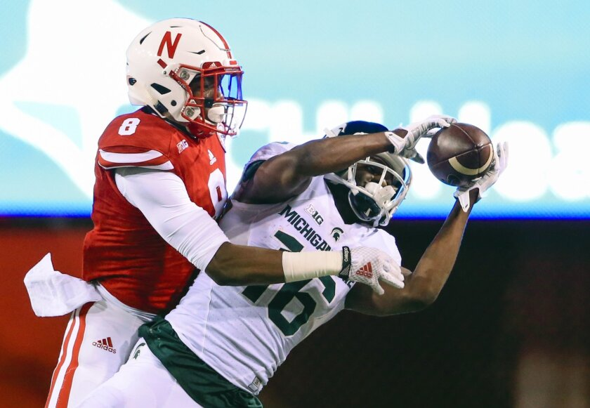 Michigan State quarterback wide receiver Aaron Burbridge (16) makes a catch in front of Nebraska defensive back Chris Jones (8) during the first half of an NCAA college football game in Lincoln, Neb., Saturday, Nov. 7, 2015. (AP Photo/Nati Harnik)