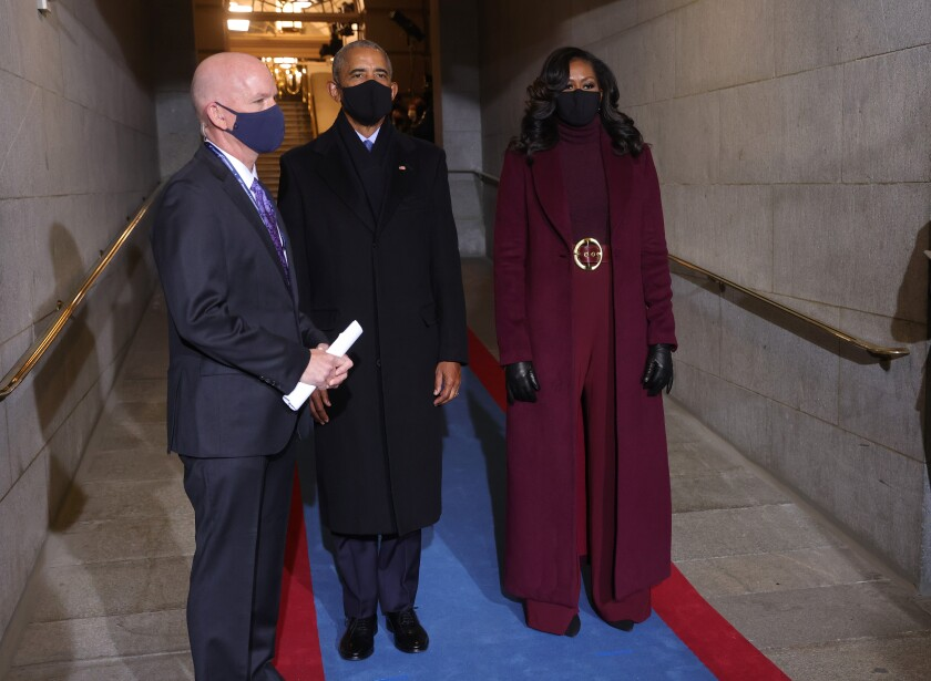 Inauguration official Tim Mitrovich guides former President Barack Obama and Michelle Obama to the Jan. 20 swearing-in