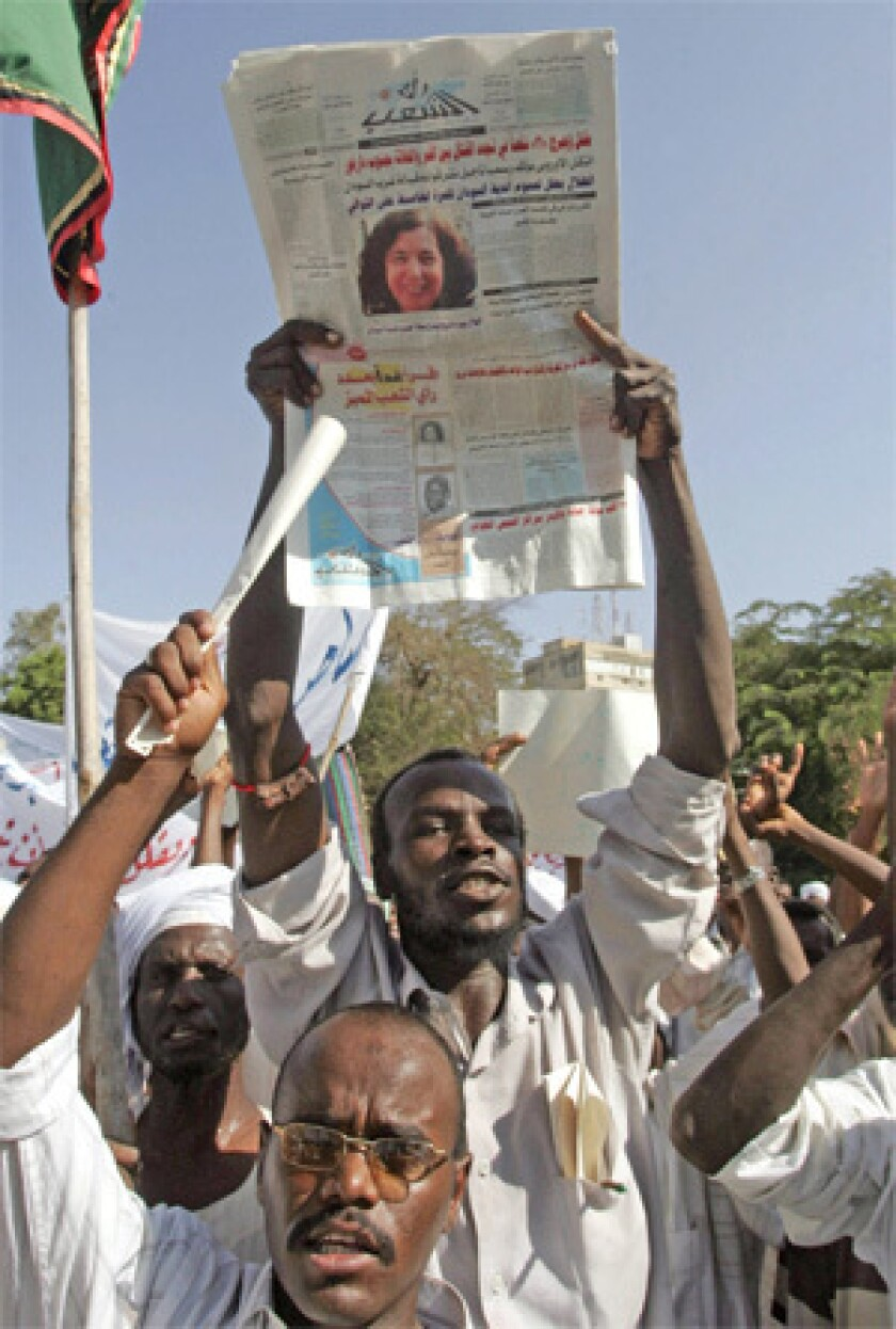 ANGER IN KHARTOUM: A Sudanese demonstrator holds a newspaper with a photo of Briton Gillian Gibbons, who was convicted of insulting Islam. Some wanted her executed.
