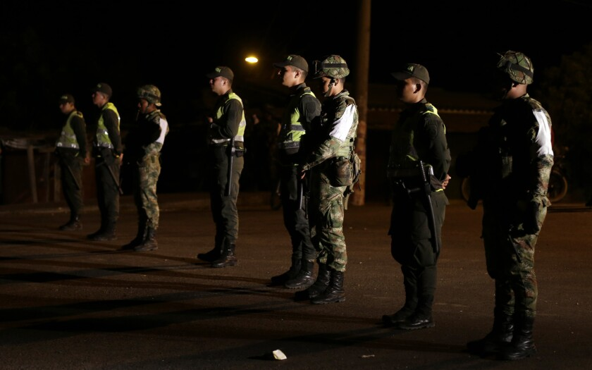 Colombian police officers and soldiers stand guard in the town of Paraguachon along the border with Venezuela on Sept. 8.