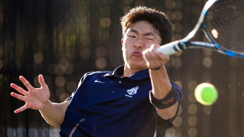 Newport Harbor's David Lee returns a forehand against Corona del Mar's Kyle Pham during the Battle o