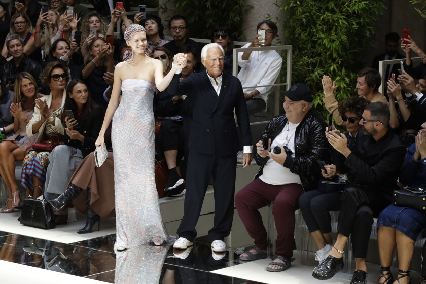 Designer Giorgio Armani, center right, poses with a model as he accepts applause at the conclusion of the Armani Spring-Summer 2020 collection, unveiled during the fashion week, in Milan, Italy, Saturday, Sept. 21, 2019. (AP Photo/Luca Bruno)