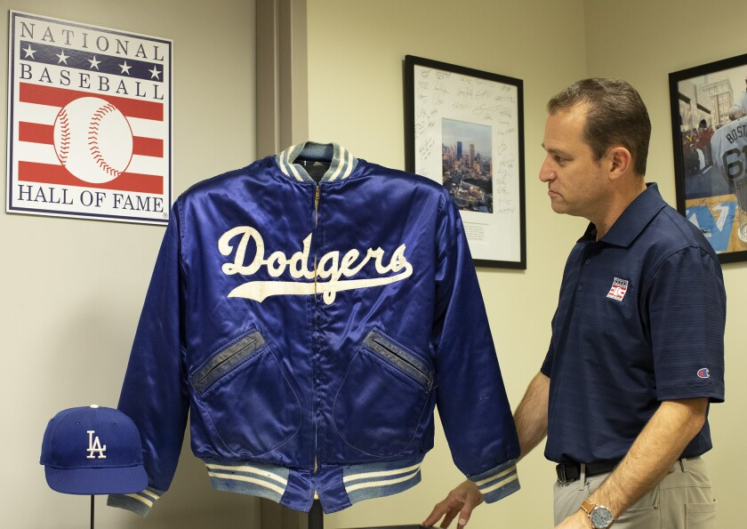 Josh Rawitch looks at a jacket and cap belonging to Dodgers legend Duke Snider.