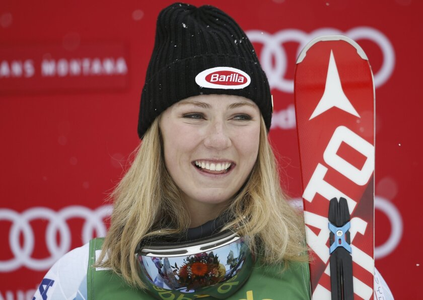 Mikaela Shiffrin, of the United States, smiles on the podium after winning an alpine ski, women's World Cup slalom, in Crans Montana, Switzerland, Monday, Feb. 15, 2016. (AP Photo/Alessandro Trovati)