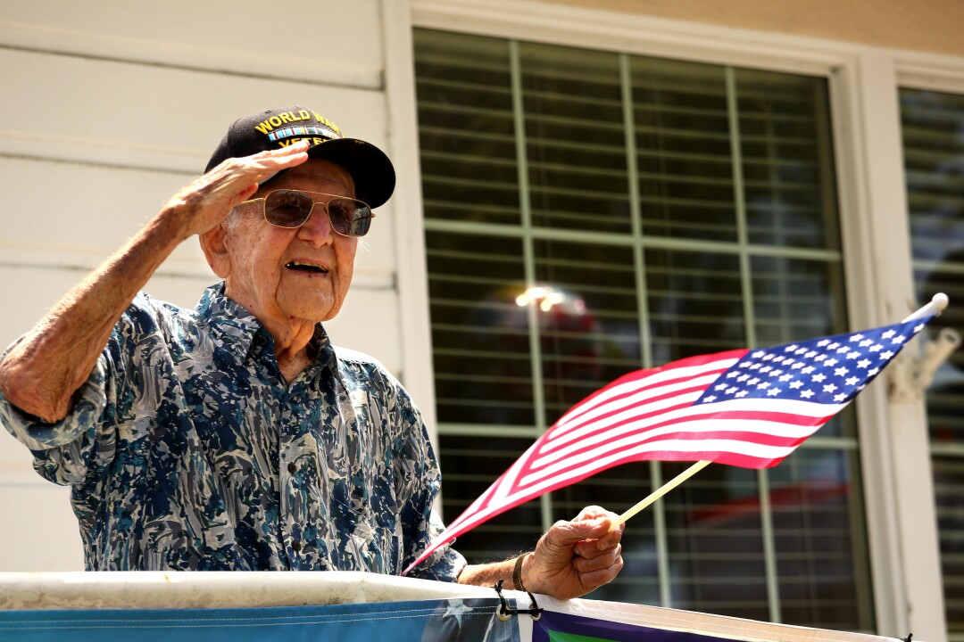 Lt. Col. Sam Sachs, a World War II veteran, salutes well-wishers during a processional outside his Lakewood assisted living home to celebrate his 105th birthday.