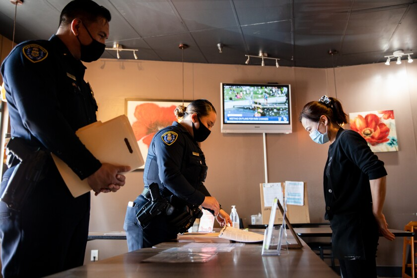 Officer Sharon Jung provides information about hate crimes to a worker at Go Go Sushi & Ramen in Mira Mesa on April 15, 2021.