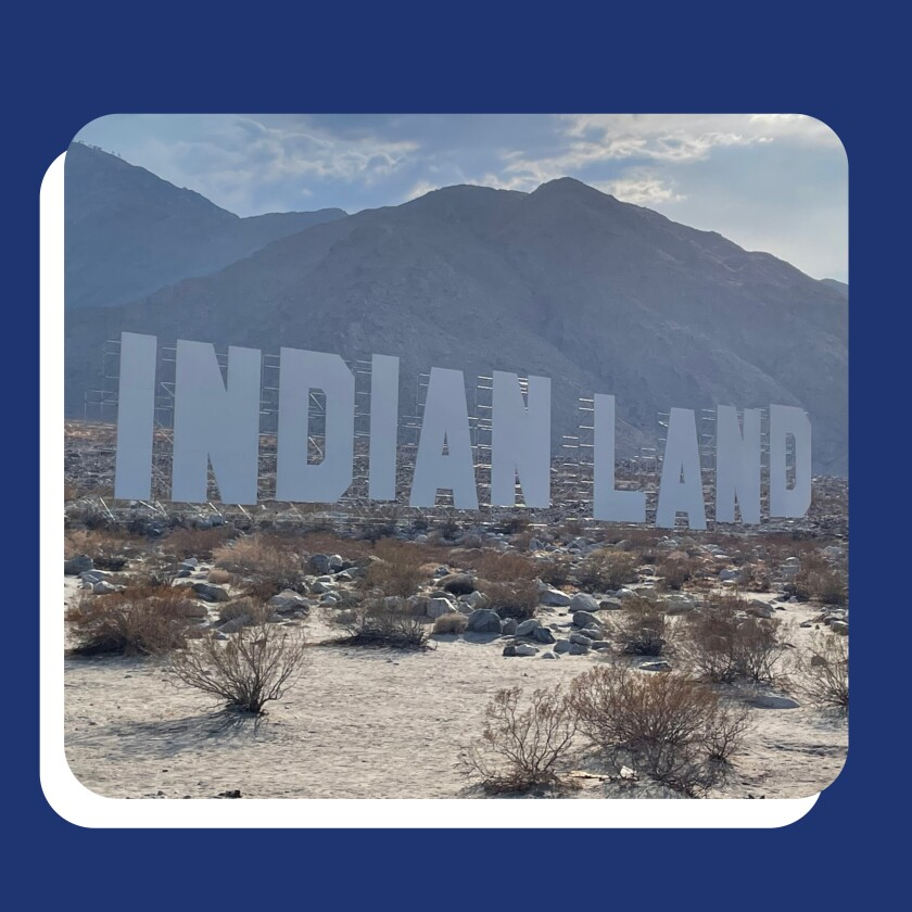 """The artwork """"Never Forget"""" features large letters spelling """"Indian Land"""" in front of a mountain range."""