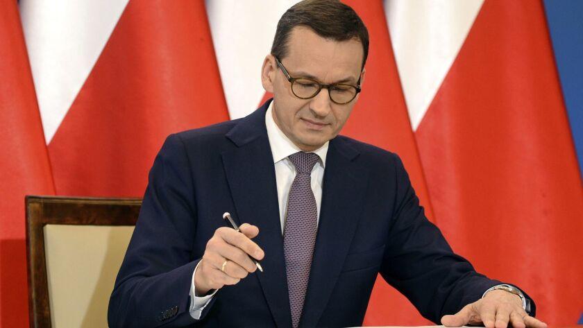 Polish Prime Minister Mateusz Morawiecki signs an agreement between Poland and Israel.