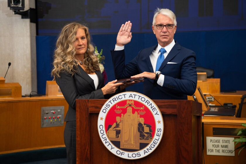 George Gascón takes the oath of office beside his wife