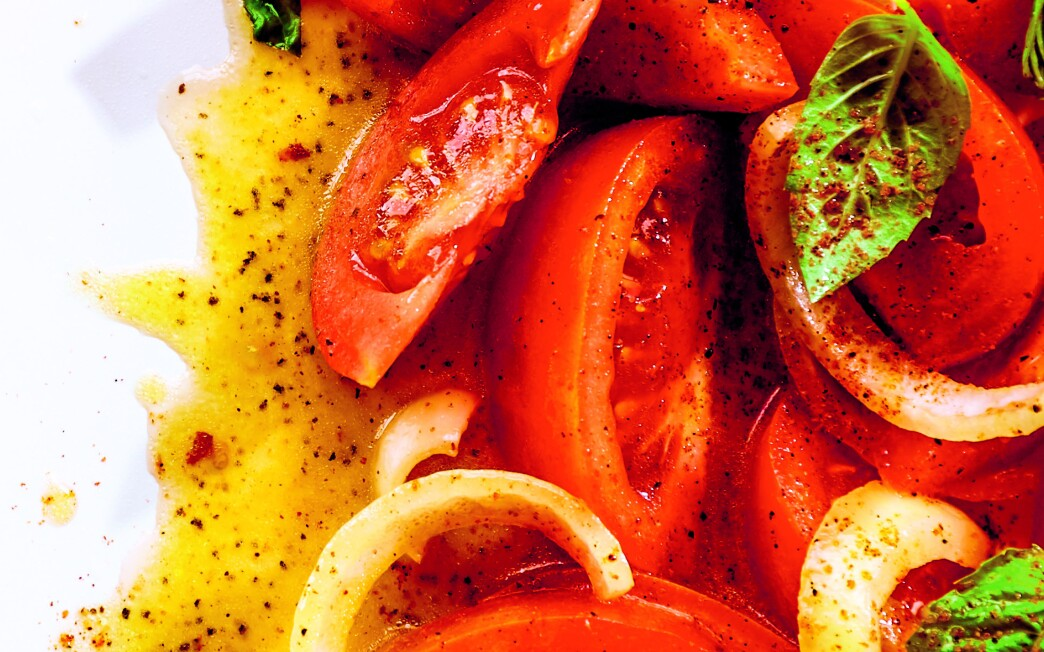 Sliced tomatoes and onions with basil and dressing flecked with chili flakes and cayenne